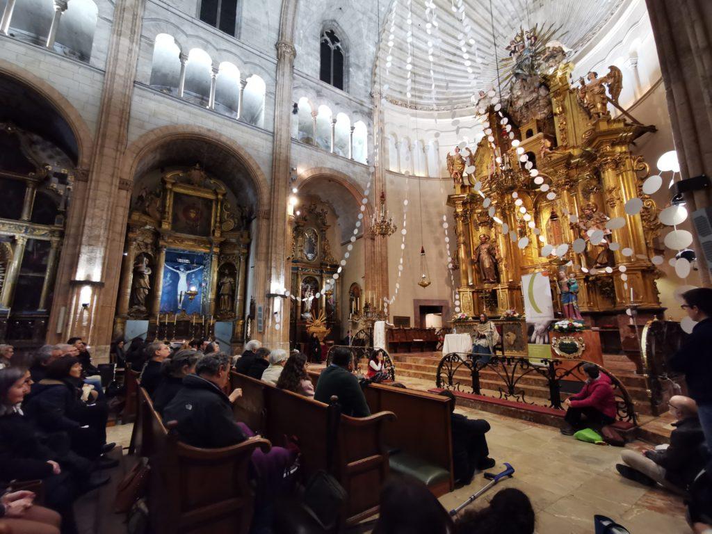 Vista de la iglesia de San Nicolás de Palma, parte de los bancos llenos de gente, y María del Himalaya dando una charla desde una mesita junto al altar.