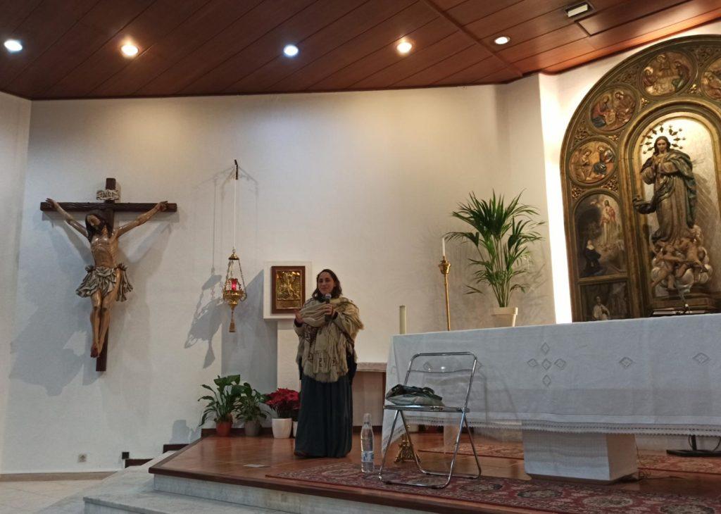 María del Himalaya habla por un micrófono. junto al altar de la parroquia de Nuestra Señora del Rosario en Ibiza, con un gran crucifijo al fondo.