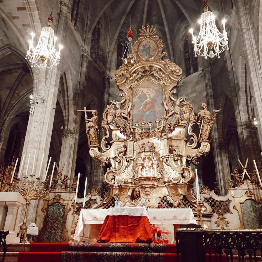 Panorámica del retablo de la iglesia de Santa Eulalia de Palma, con María del Himalaya tras el altar dando una charla.